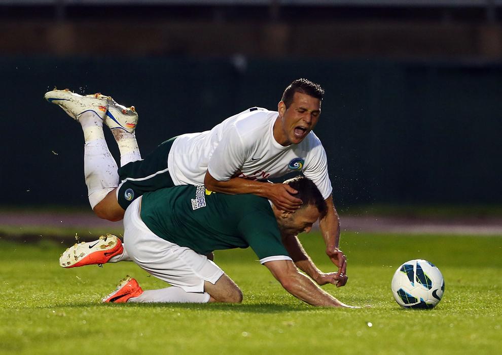 Peri Marosevic, de la New York Cosmos, este atacat de Matt Svanda, de la Newtown Pride FC, în timpul meciului de caritate pentru Newtown Parent Connection pe stadionul Veterans Memorial din New Britain, Connecticut, SUA, marţi, 18 iunie 2013.