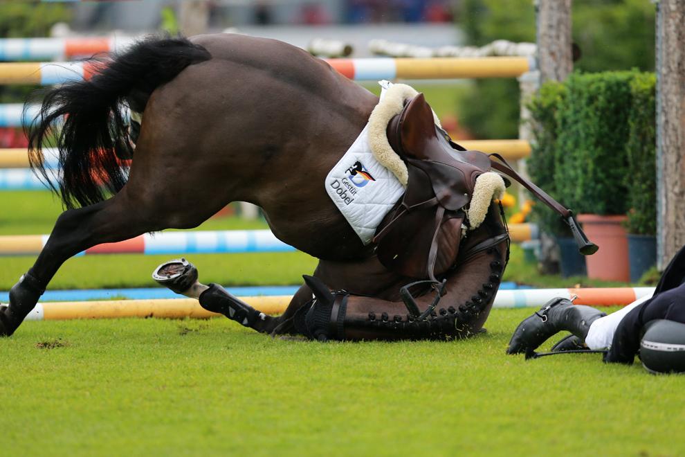 Călăreţul german Andreas Kreuzer şi calul său Balounito cad după ce încearcă să sară peste un obstacol, în timpul competiţiei de sărituri peste obstacole Prize of North Rhine-Westphalia, parte a festivalului de echitaţie CHIO World Equestrian Festival din Aachen, Germania, vineri, 28 iunie 2013.