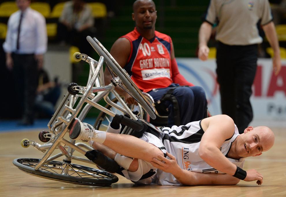 Jucătorul britanic Abdillah Jama priveşte în timp ce căpitanul echipei germane, Sebastian Wolk, cade pe podea, în timpul meciului din Grupa A a preliminariilor Campionatului European de Baschetbal în Scaun cu Rotile 2013, din Frankfurt, Germania, vineri, 28 iunie 2013.