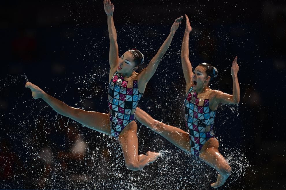 Două înotătoare din echipa Japoniei de înot sincron sar în aer, în timpul probei tehnice pe echipe din cadrul Campionatelor Mondiale Fina, desfăşurate în Barcelona, luni, 22 iulie 2013.