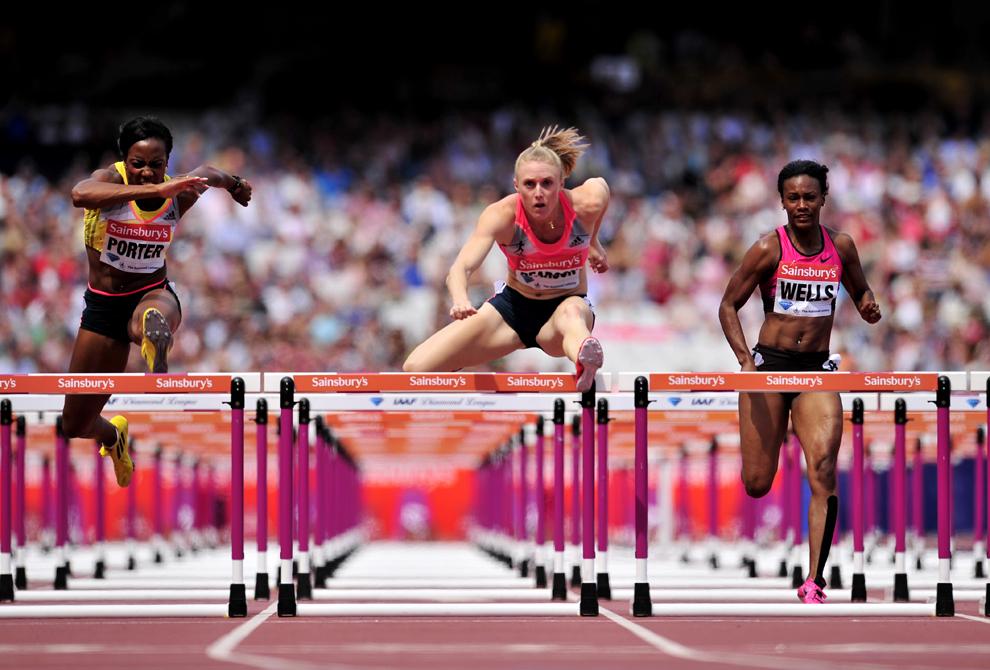 Tiffany Porter (S) din Marea Britanie, alături de Sally Pearson (C) din Australia si Kellie Wells (D) din SUA concurează în timpul probei de 100 de metri garduri, din cadrul campionatelor IAAF Diamond League International Athletics, pe Stadionul Olimpic din Londra, sâmbătă, 27 iulie 2013.