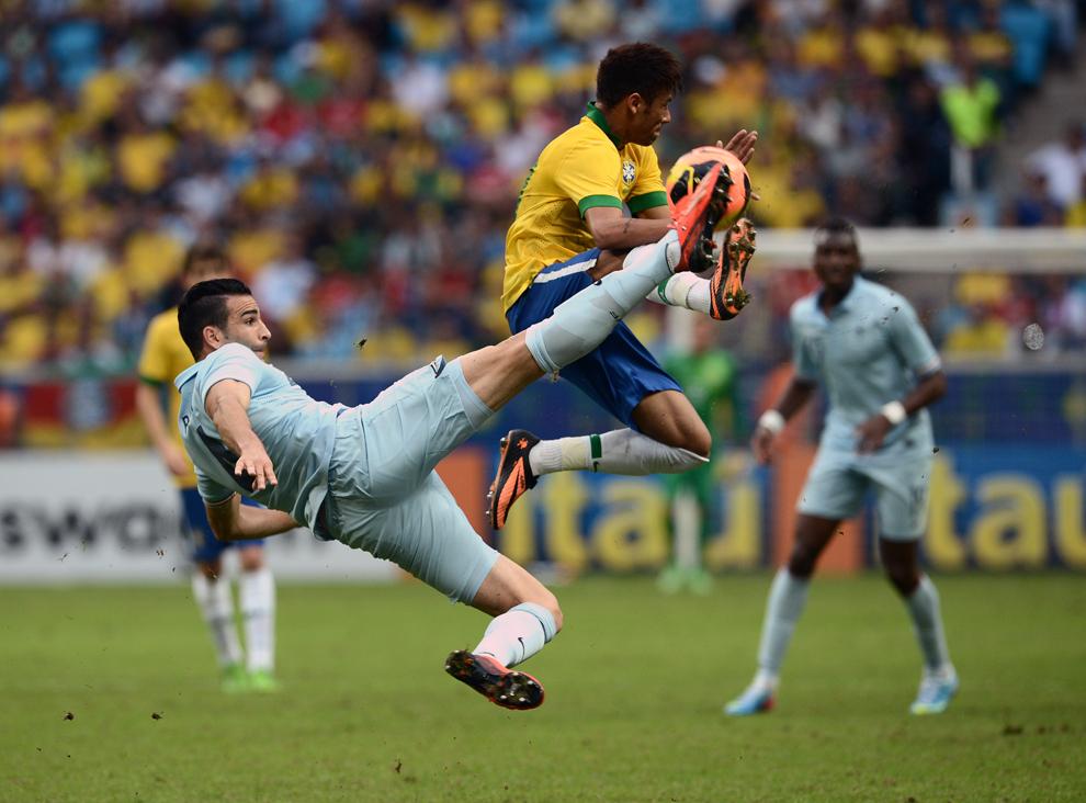 Atacantul Braziliei, Neymar (C), dispută balonul cu fundaşul Franţei, Adil Rami (S), în timpul meciului amical Brazilia vs Franţa, de pe Arena Gramio Stadium, din Porto Alegre, Brazilia, sâmbătă, 8 iunie 2013.