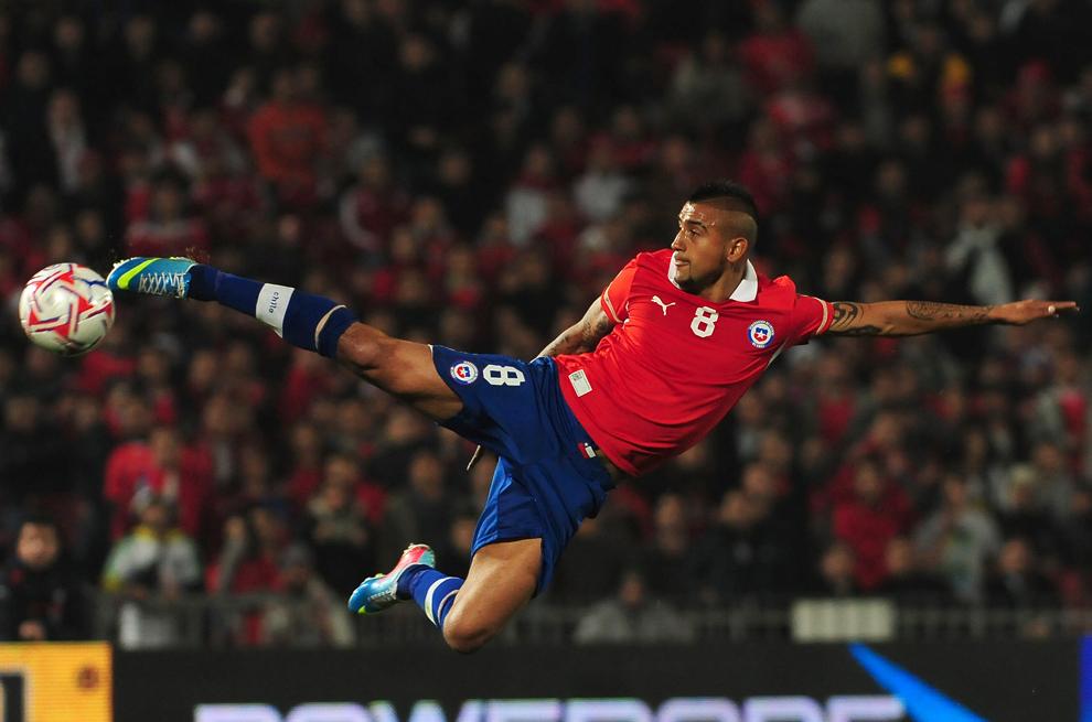 Jucătorul echipei Chile, Arturo Vidal, loveşte balonul în timpul meciului împotriva Boliviei, în timpul meciului de calificare pentru FIFA World Cup Brazil 2014 South American, pe Stadionul Naţional din Santiago, Chile, marţi, 11 iunie 2013.