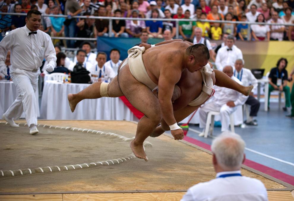 Doi luptători de sumo concurează la categoria grea, în timpul Jocurilor Mondiale de Sumo, în Cali, Columbia, vineri, 26 iulie 2013.