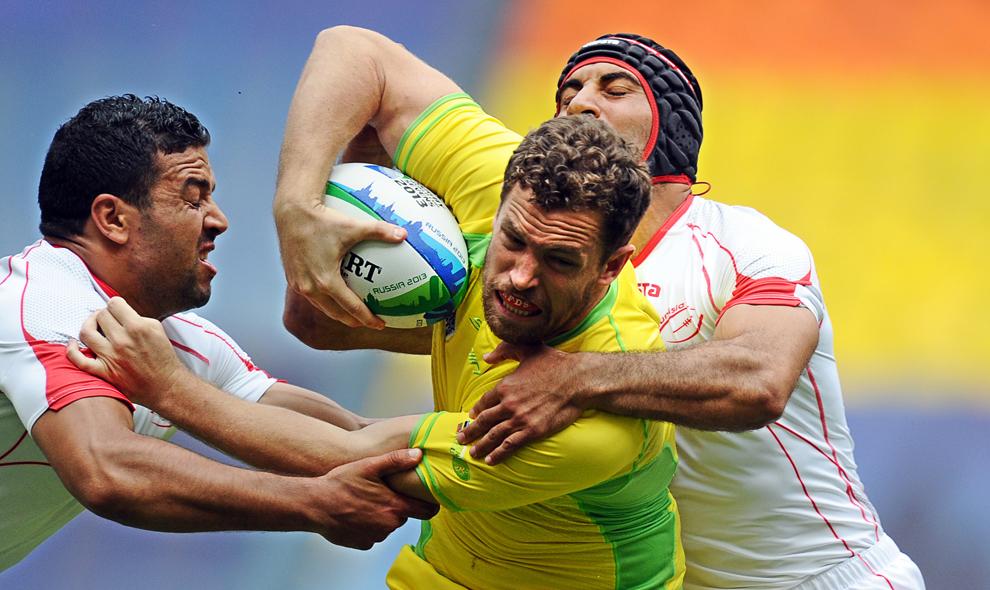 Jucătorii Tunisiei Aymen Gloulou (S) şi Chems Eddine Khalifa (D) dispută balonul cu jucătorul australian Luke Morahan (C), în timpul meciului Tunisia vs Australia din campionatul de rugby 2013 Rugby World Cup Sevens, din Moscova, Rusia, sâmbătă, 29 iunie 2013.