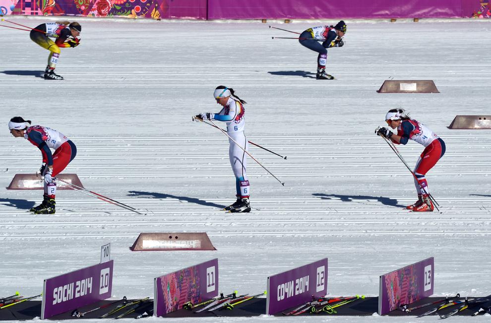 Marit Bjoergen din Norvegia (S),  Charlotte Kalla (C) din Suedia şi Heidi Weng din Norvegia (D) aşteaptă predarea ştafetei, în timpul probei de schi fond 7,5km + schiatlon 7,5km din cadrul  Jocurilor Olimpice de Iarnă în Rosa Hutor, Rusia, sâmbătă, 8 februarie 2014.