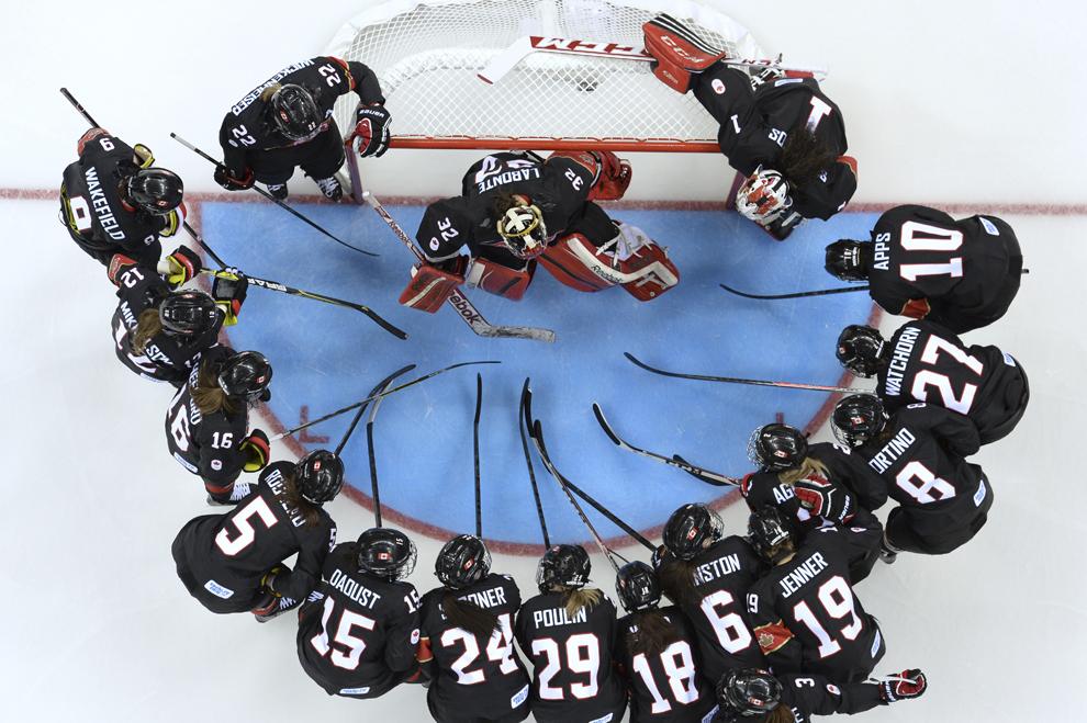 Jucătoarele echipei de hochei a Canadei, discută înaintea începerii meciului împotriva echipei Elveţiei, în timpul Jocurilor Olimpice de Iarnă, în Soci, Rusia, sâmbătă, 8 februarie 2014.