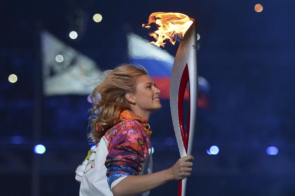 Maria Sharapova aleargă cu torţa olimpică, în timpul ceremoniei de deschidere a Jocurilor Olimpice de Iarnă desfăşurate în Soci, Rusia, vineri, 7 februarie 2014.
