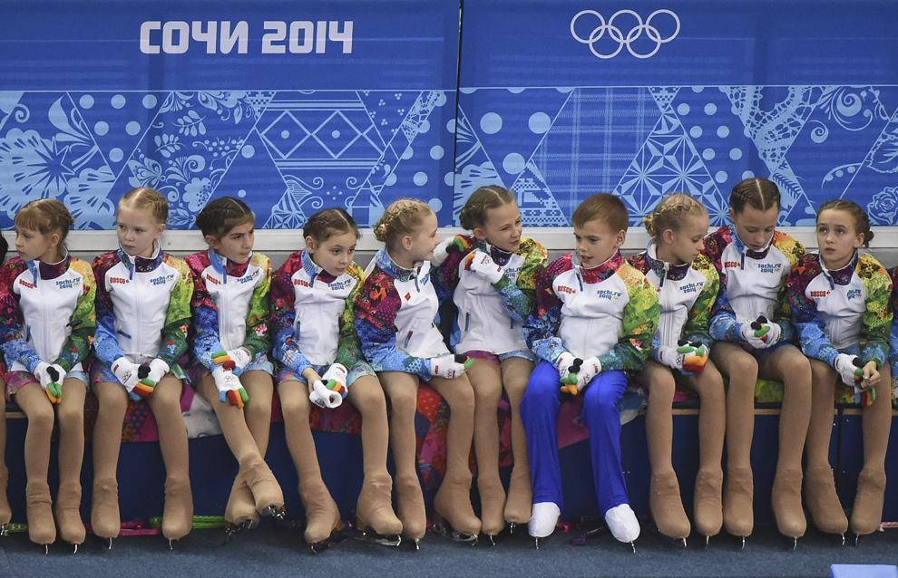 Copii care adună flori pot fi văzuţi în timpul programului de patinaj artistic program scurt din cadrul Olimpiadei de Iarnă de la Soci, 19 februarie 2014.