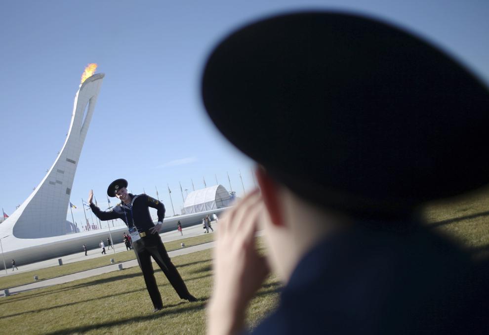 Un soldat din marina rusă pozează în faţa flăcării olimpice din Parcul Olimpic, joi, 13 februarie 2014.