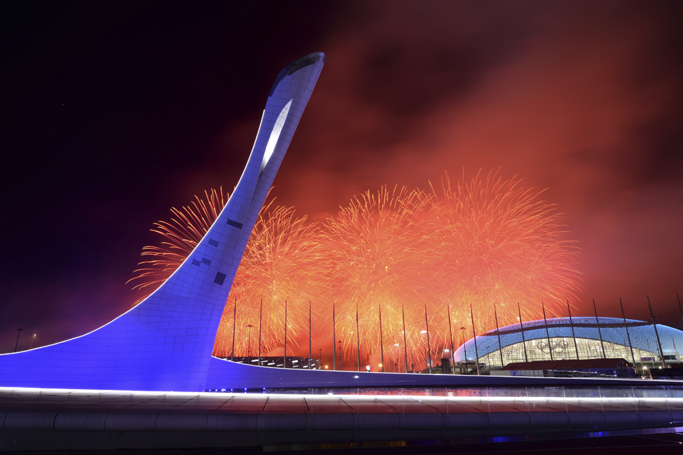 Artificii explodează în spatele Cazanului Flăcării Olimpice, după ce aceasta a fost stinsă, la finalul ceremoniei de închidere a Jocurilor Olimpice de Iarnă, in Soci, Rusia, duminică, 23 februarie 2014.