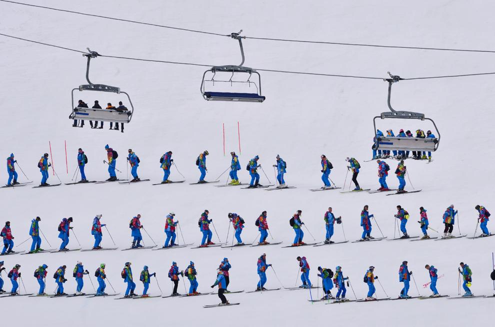 Voluntari pregătesc zăpada înaintea startului în proba masculină de schi alpin super slalom combinat, în timpul Olimpiadei de Iarnă de la Soci, februarie 14, 2014.