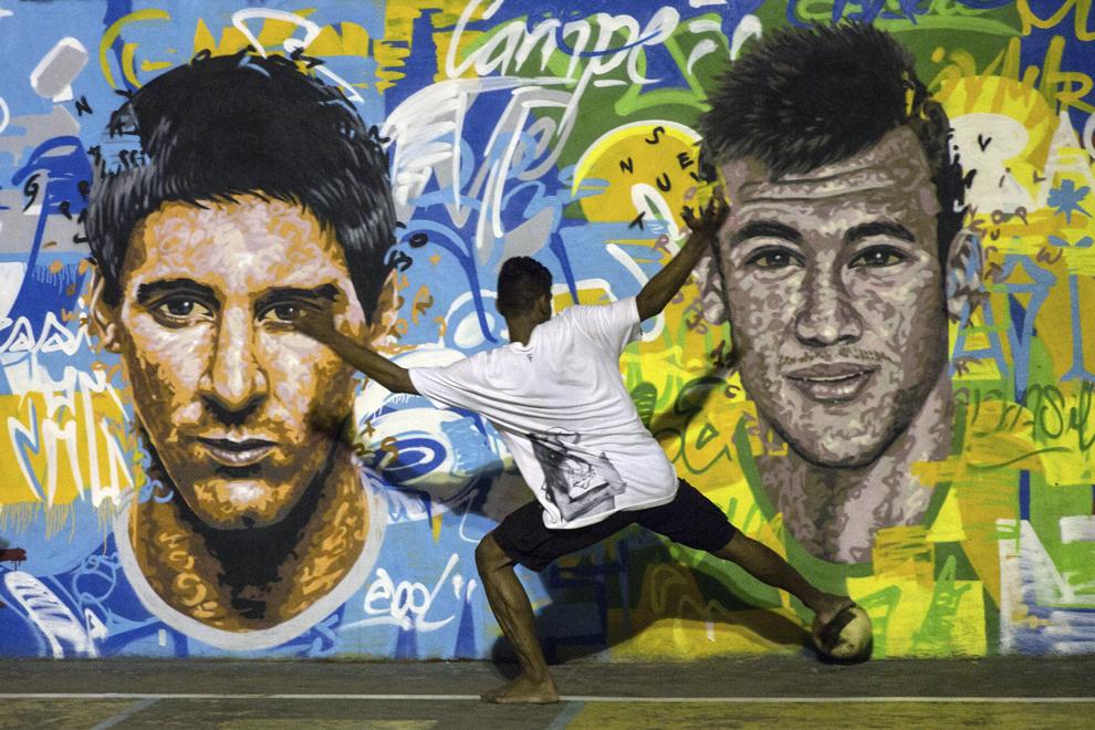 Un tânăr joacă fotbal în faţa unei picturi murale care îi reprezintă pe jucătorul de fotbal argentinian Lionel Messi (S) şi jucătorul brazilian Neymar da Silva Santos Junior, în suburbia Tavares Bastos (favela) oraşului Rio de Janeiro, Brazilia, duminică, 8 iunie 2014.