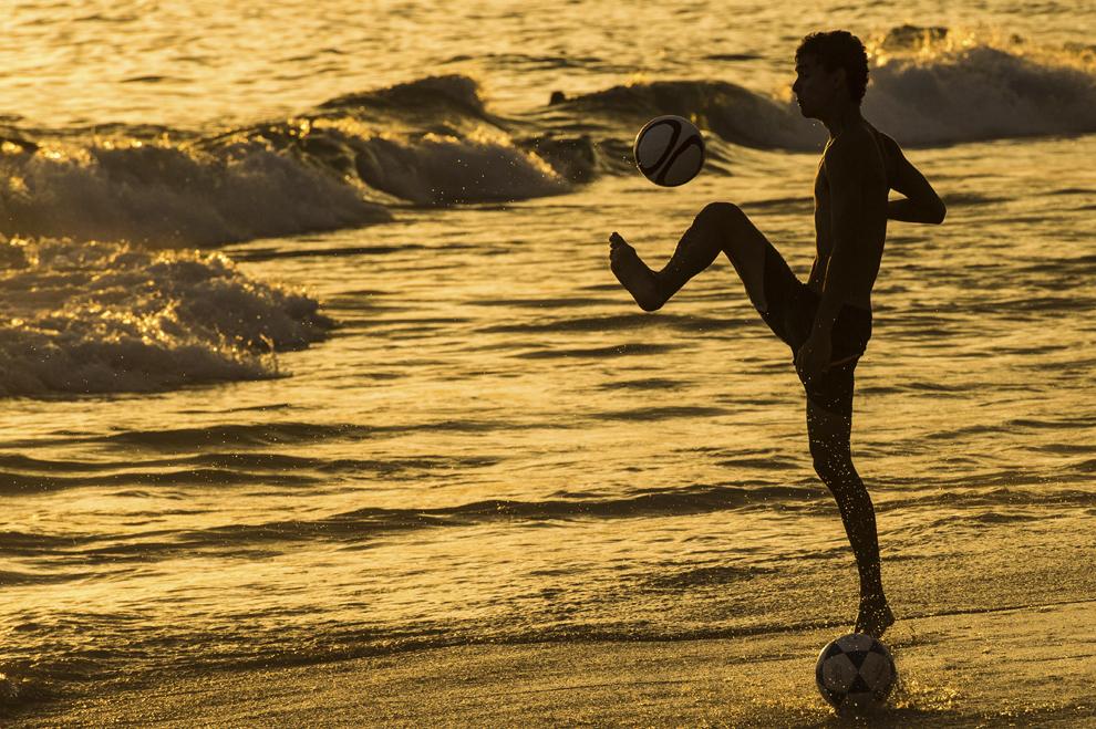 Un bărbat joacă fotbal în lumina apusului, la Ipanema Beach, în Rio de Janeiro, Brazilia, la 9 ianuarie 2014.