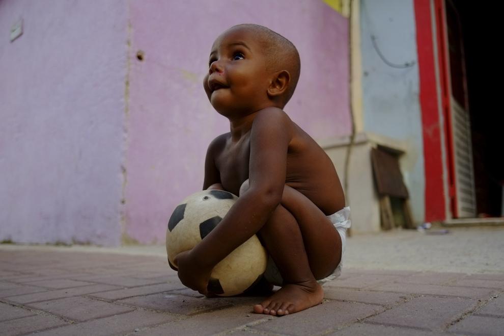 Un băieţel ţine o minge de fotbal, în Cidade de Deus (Oraşul lui Dumnezeu), favela în Rio de Janeiro, la 23 ianuarie 2014.