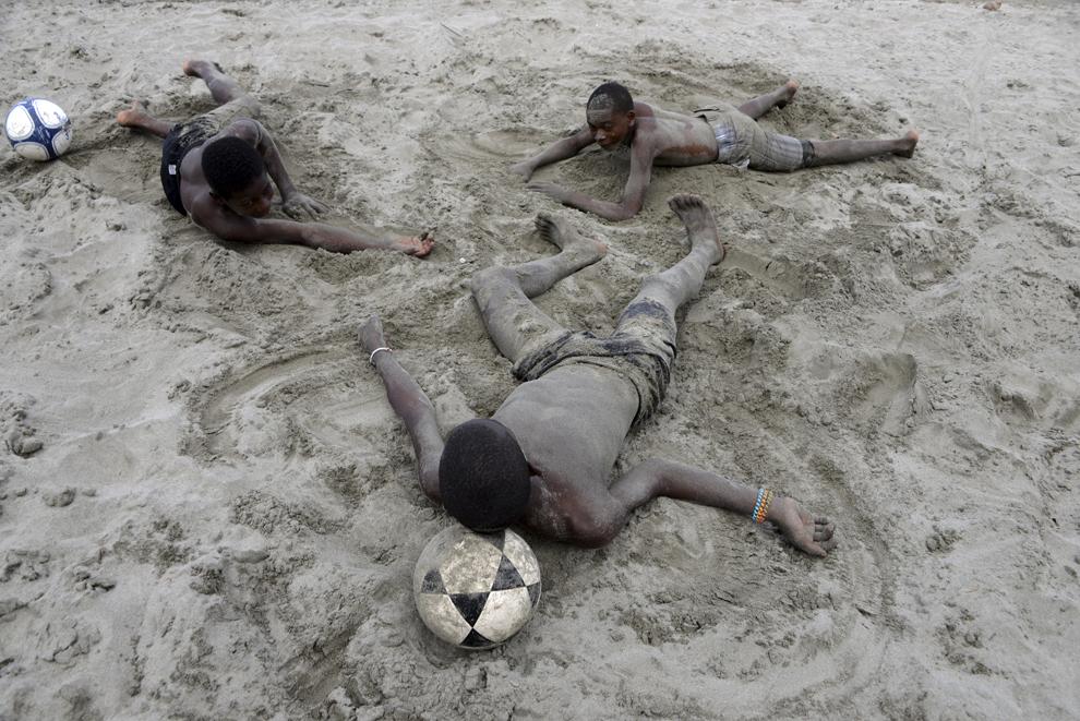 Trei copii, membri ai comunităţii Gaifuna, se odihnesc după ce au jucat fotbal pe plaja El Triunfo de la Cruz de la Marea Caraibilor, 300 km nord de Tegucigalpa, la 10 februarie 2014.