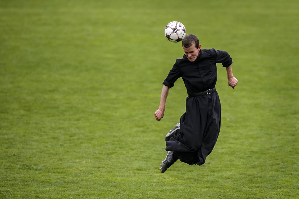 Un seminarist al Seminarului Internaţional al Sfântului Pius al X-lea loveşte mingea cu capul, în timpul unui meci de fotbal, la 25 mai 2014, în Riddes, vestul Elveţiei.