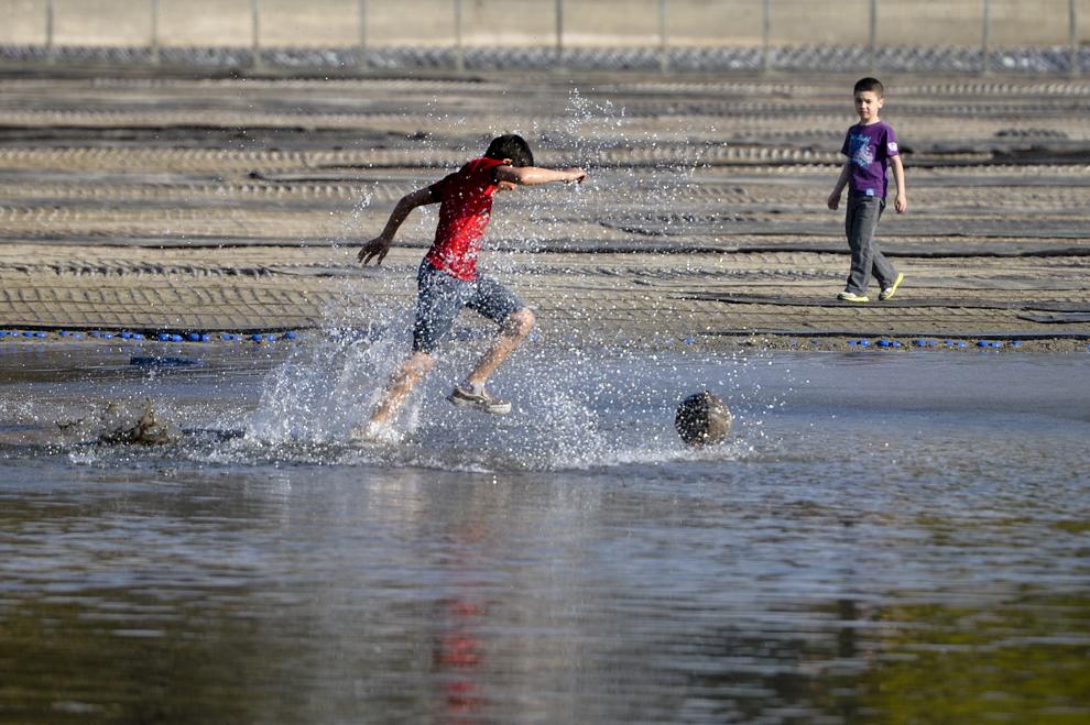 Un copil aleargă după o minge prin lacul Cişmigiu din Bucureşti, sâmbătă, 13 aprilie 2013.