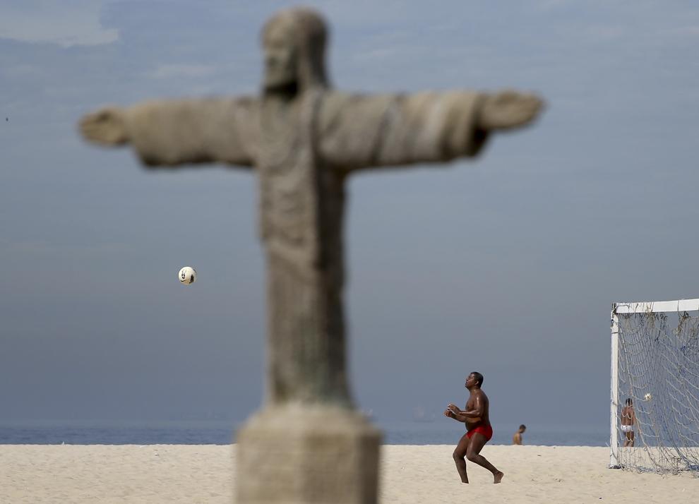 Rolando Byano joacă fotbal pe plaja Copacabana, lângă o sculptură în nisip, replica a celebrei statui a lui Isus, în Rio de Janeiro, sâmbătă, 7 iunie 2014.