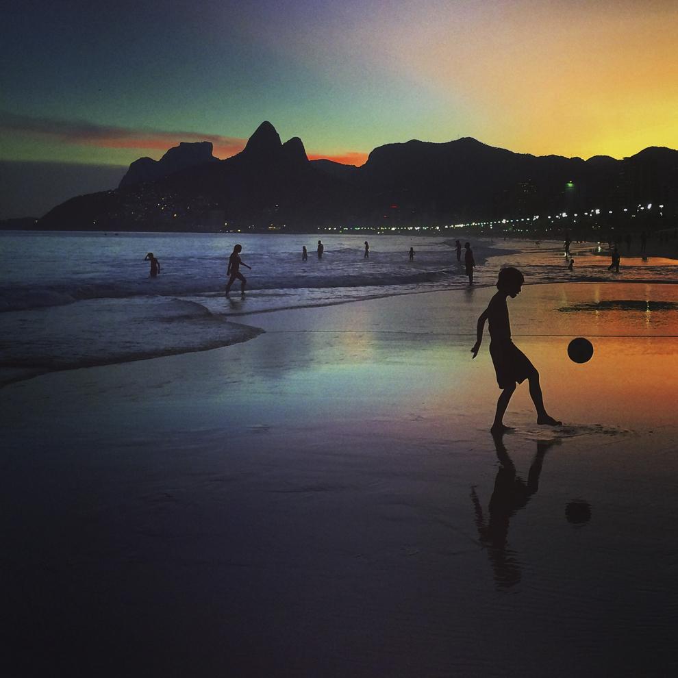 Imagine creată folosind filtre digitale – Un băiat joacă fotbal în lumina asfinţitului, în Rio de Janeiro, Brazilia, duminică, 8 iunie 2014.