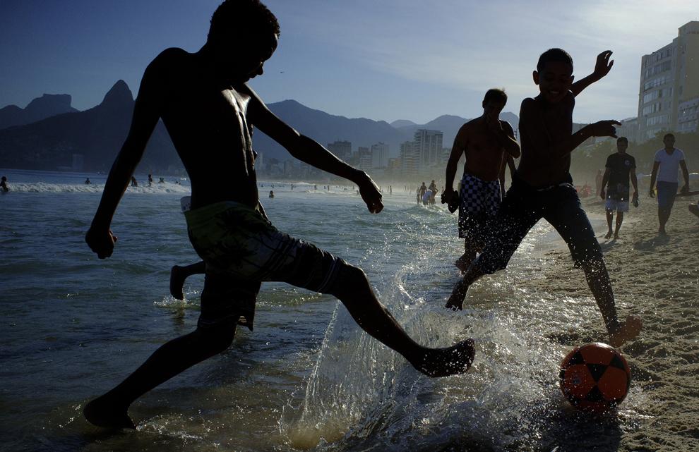 Un grup de copii joaca fotbal pe plaja Ipanema, în  Rio de Janeiro, Brazilia, duminică, 8 iunie 2014.