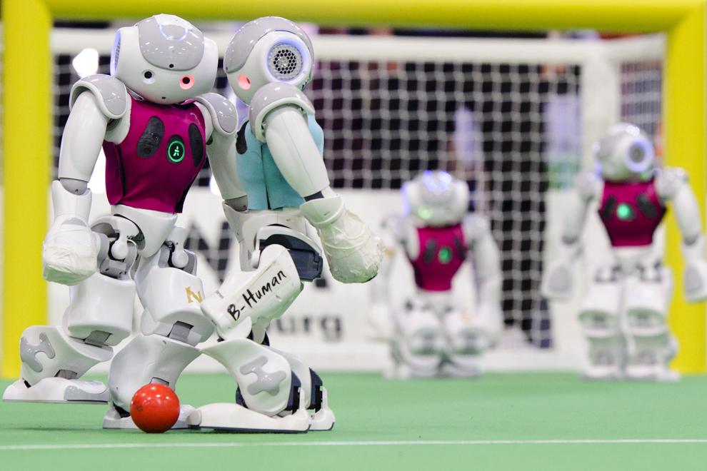Două echipe de roboţi joacă una împotriva celeilalte în cadrul turneului RoboCup German Open, în Magdeburg, Germania, pe 3 aprilie 2014.