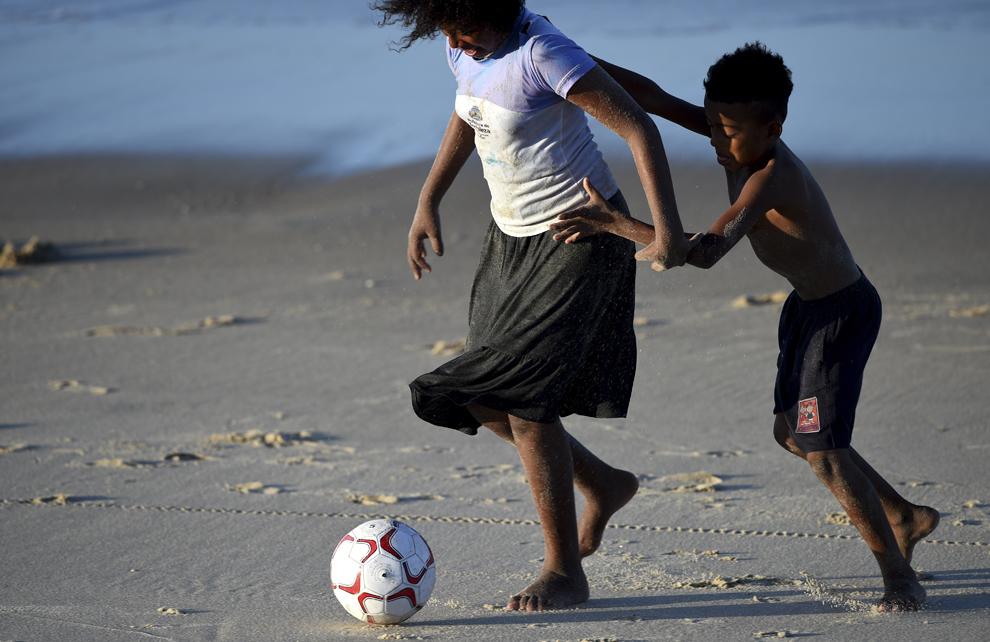 Un băiat şi o fată joacă fotbal pe plajă, în Fortaleza, Brazilia, luni, 9 iunie 2014.