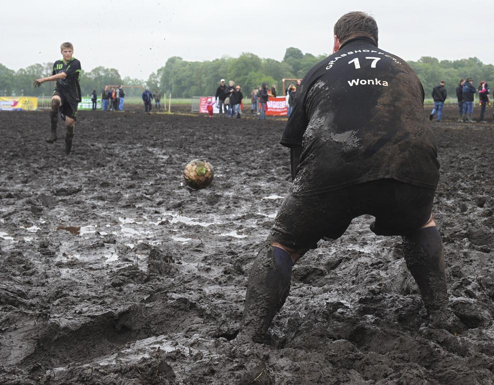 """Un jucător al echipei Borkum """"Freestyler"""" (S) se pregăteşte să execute un penalty împotriva portarului echipei """"Grashopper"""" (D) în timpul unui meci contând pentru Second German Open Swamp Football Championship, pe 26 mai 2013, în Rieste, vestul Germaniei."""
