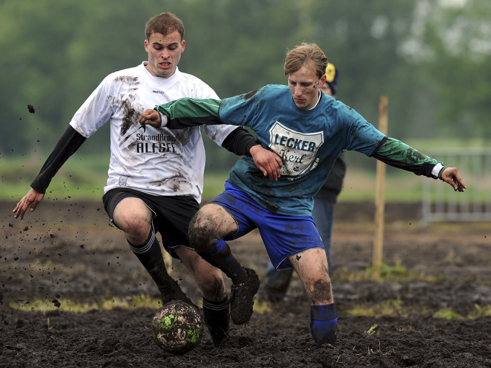 """Un jucător al echipei Iserlohn """"Grashopper"""" (D) se luptă pentru balon cu un jucător al echipei """"Moormonen"""" (S) în timpul unui meci din cadrul Second German Open Swamp Football Championship, pe 26 mai 2013, în Rieste, vestul Germaniei."""