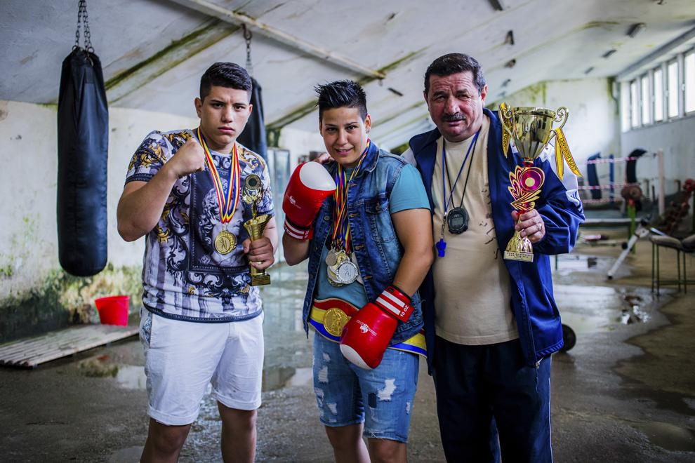 Alexandru Ciociu, medaliat cu bronz la naţionalele de cadeţi la categoria +80 kg în 2013 şi argint la campionatele naţionale din 2014, Irina Stoica, 27 ani, campioană naţională în 2013 şi câştigătoarea Cupei României (la 60 kg) în 2014, şi antrenorul Emil Bihorean se fotografiază cu o parte din trofeele obtinute, miercuri, 30 iulie 2014.