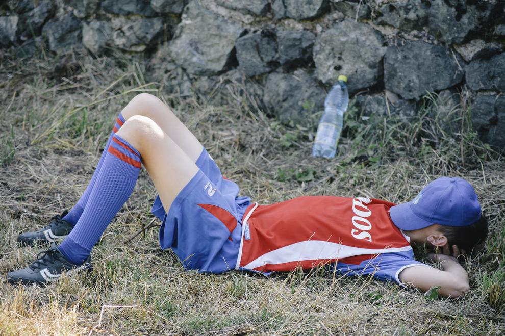 Un tanar se odihneste la finalul unui meci de in cadrul Cupei Satelor la Oina, in Savarsin, duminica 9 august 2015.