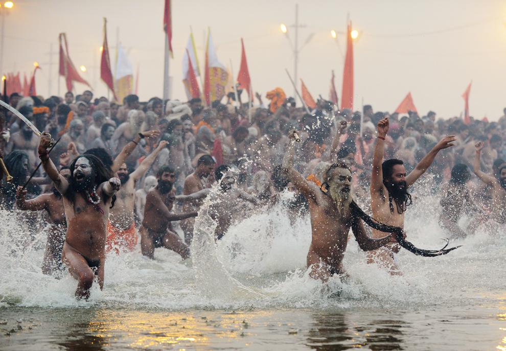 Sadhuşi (Oameni sfinţi) aleargă în Sangam, la confluenţa râurilor Yamuna, Gange şi Sarawati, în timpul pelerinajului Kumbh Mela, în Allahabad, sâmbătă, 14 ianuarie 2013. (Roberto Schmidt / AFP)