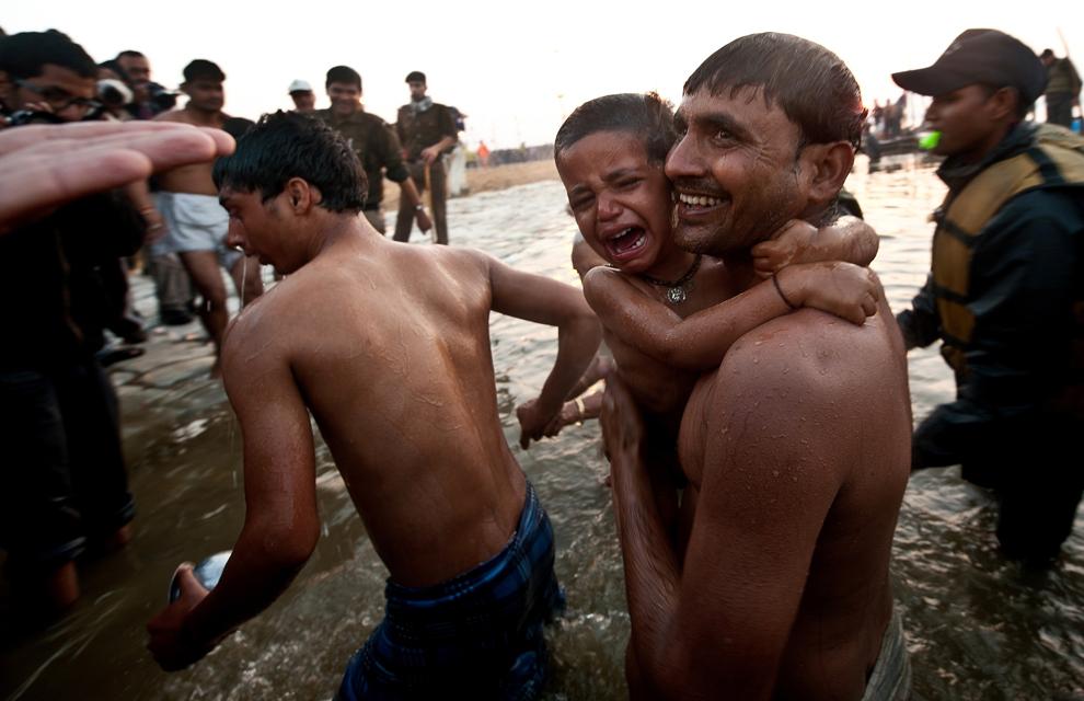 Un copil plânge după ce a fost scufundat în Sangam, la confluenţa râurilor Yamuna, Gange şi Sarawati cu ocazia zilei de bun augur Mauni Amavasya, în timpul pelerinajului Kumbh Mela din Allahabad, marţi, 10 februarie 2013. (Manan Vatsyayna / AFP)