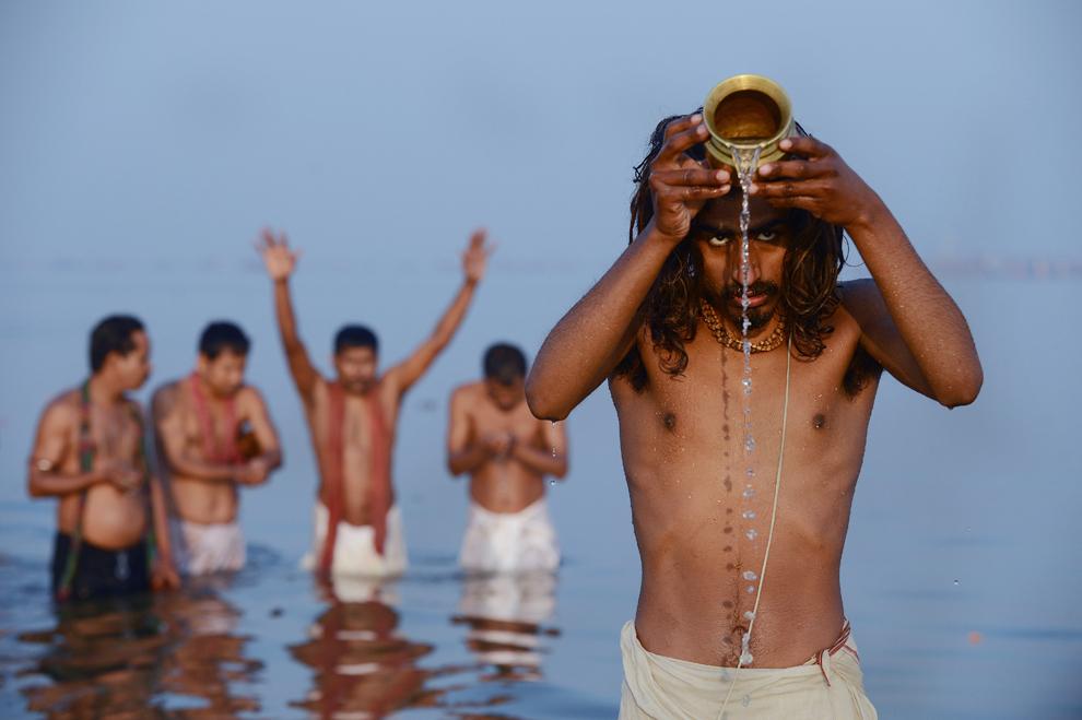 Adepţi hinduşi se roagă în timp ce se îmbăiază în Sangam, la confluenţa râurilor Yamuna, Gange şi Sarawati, cu ocazia zilei de bun augur, Mauni Amavasya, în timpul Kumbh Mela din Allahabad, marţi, 10 februarie 2013. (Roberto Schmidt / AFP)