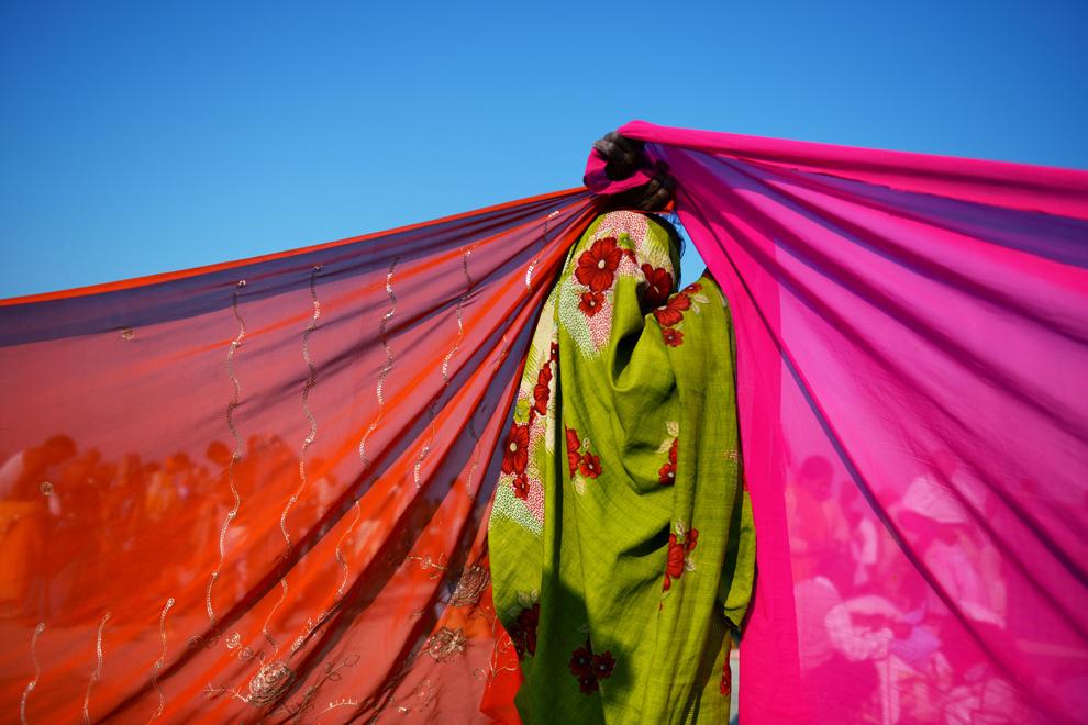 O femeie ţine ridicate colţurile a doua sari pentru a le usca, la confluenţa râurilor Yamuna, Gange si Saraswati, la Kumbh Mela în Allahabad, duminică, 10 februarie 2013. (Roberto Schmidt / AFP)