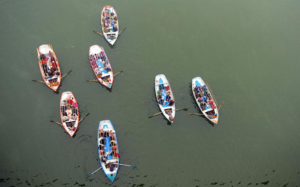Pelerini hinduşi călătoresc cu barca pentru a se îmbăia în Sangam, la confluenţa râurilor Gange, Yamuna şi Saraswati, în timpul pelerinajului Kumbh Mela, miercuri, 23 ianuarie 2013. (Robert Schmidt / AFP)