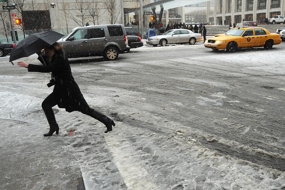 O femeie trece pe o stradă acoperită de noroi, în New York, vineri, 08 februarie 2013, în timpul unei furtuni care afectează nord-est-ul SUA. (Mehdi Taamallah / AFP)