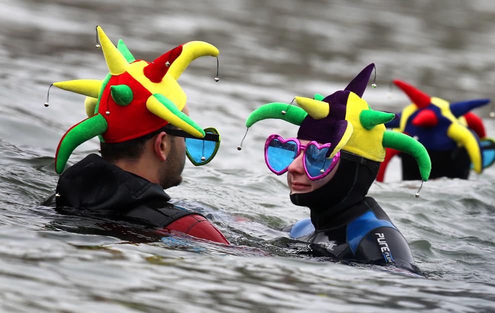 Un bărbat şi o femeie îmbrăcaţi în scafandri, purtând pălării cu clopoţei şi ochelari în formă de inimioare, participă la a 44 a ediţie a concursului de înot în Dunăre, în Neuburg, Germania, sâmbătă, 26 ianuarie 2013. (Karl-Josef Hildenbrand / AFP)