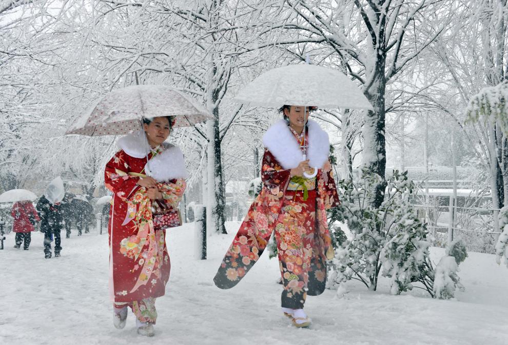 Două femei de douăzeci de ani, îmbrăcate în kimono, se plimbă pe o stradă acoperită cu zăpadă, în Tokyo, luni, 14 ianuarie 2013. (Yoshikazu Tsuno / AFP)