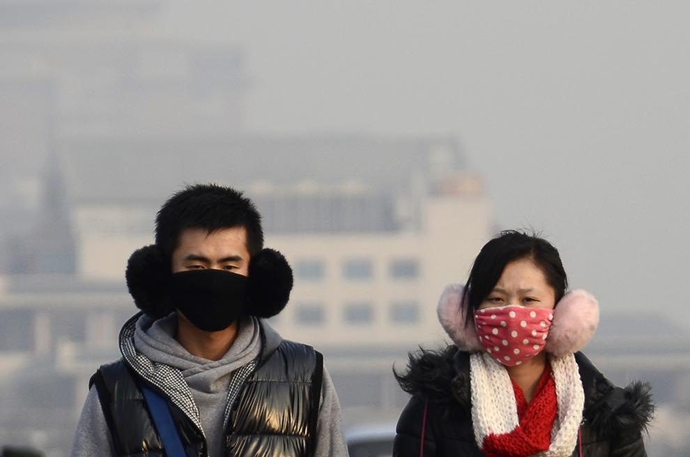 Un cuplu ce poartă măşti de faţă priveşte înainte în timp ce se deplasează pe o stradă din Beijing, marţi, 15 ianuarie 2013. (Wang Zhao / AFP)