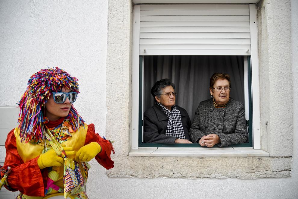 O femeie costumată în clovn stă lângă o fereastră deschisă în care se pot vedea doua femei ce urmăresc parada Clovnilor, în Sesimbra, Portugalia, marţi, 11 februarie 2013.