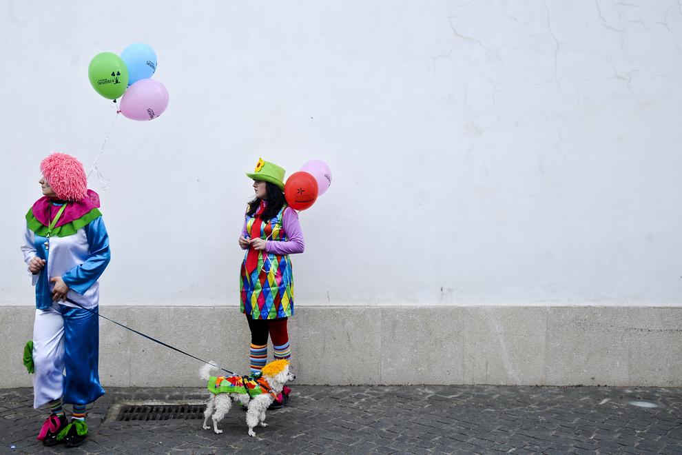 Două femei costumate în clovni plimbă un căţel deghizat, în timpul paradei Clovnilor, desfăşurată în Sesimbra, Portugalia, marţi, 11 februarie 2013.