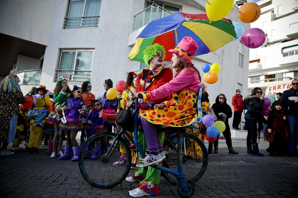 Persoane costumate în clovni dansează în timpul paradei Clovnilor, desfăşurată în Sesimbra, Portugalia, marţi, 11 februarie 2013.