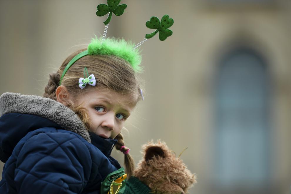 Cara, 5 ani, stă pe umerii tatălui său înaintea începerii paradei de Sfântul Patrick, organizată de Ambasada Irlandei cu ocazia Zilei Naţionale a Irlandei, în piaţa George Enescu din Bucureşti, duminică, 17 martie 2013.