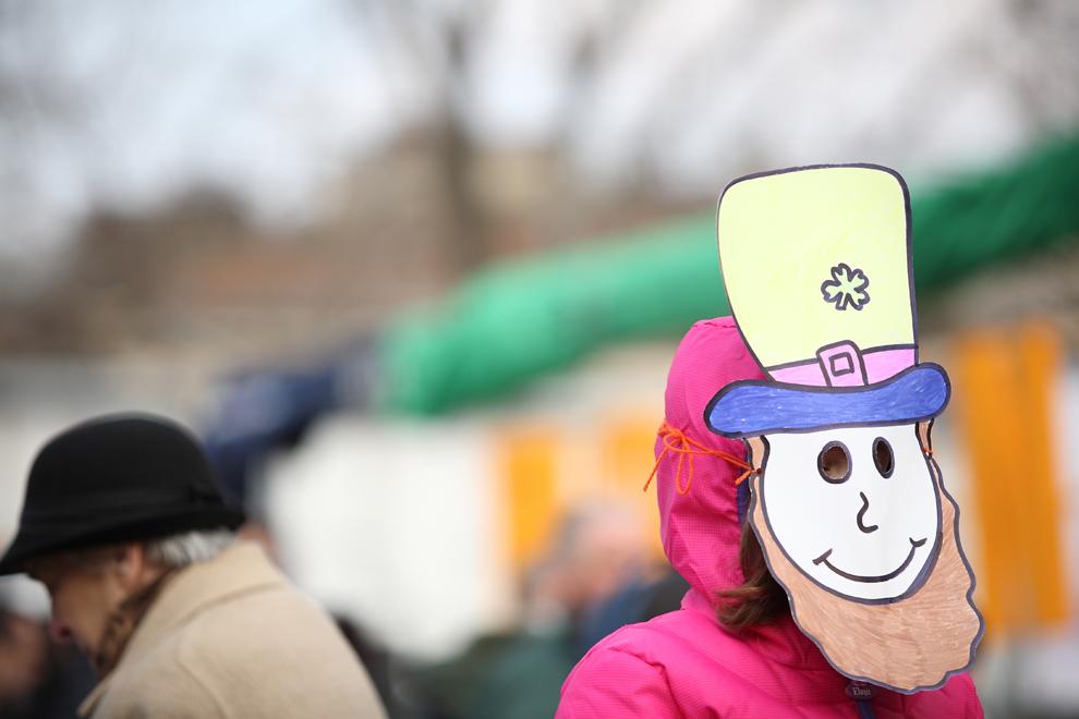 O fetiţă cu o mască din carton pe faţă urmăreşte parada organizată cu ocazia sărbătorii Sfântului Patrick, în Piaţa George Enescu din Bucureşti, duminică, 17 martie 2013.