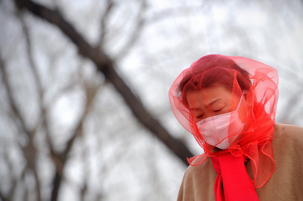 O chinezoaică îşi acoperă capul cu o eşarfă în timp ce se plimbă prin piaţa Tiananmen din Beijing, sâmbătă 9 martie 2013 din cauza furtunii de praf care a cuprins capitala chineză.