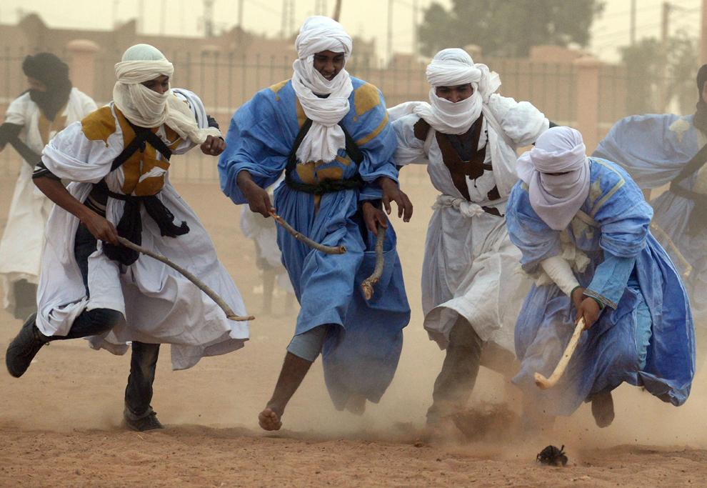 Mai mulţi bărbaţi se luptă pentru minge în timpul unui meci de hokey nomad, jucat pe nisip, în deşertul marocan, la M'hamid El Ghizlane, Maroc, sâmbătă, 16 martie 2013.