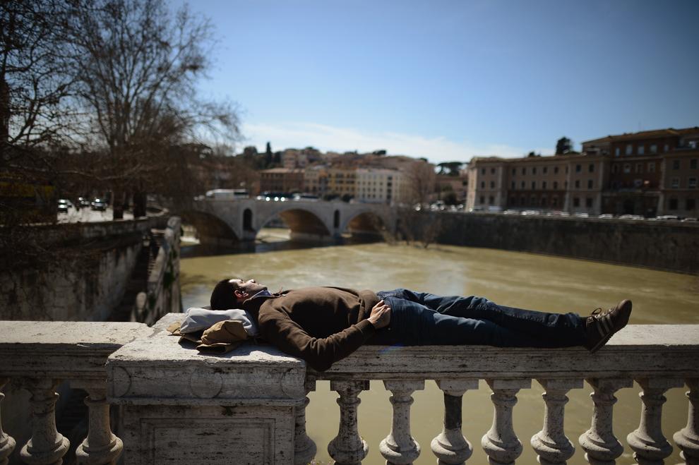 Un bărbat se odihneşte pe balustrada unui pod din centrul Romei, vineri, 22 martie 2013