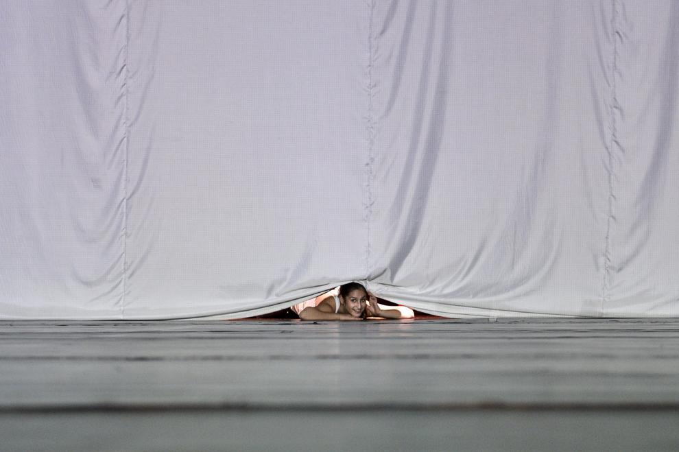 O fetiţă de la Centrul pentru Politici Roma şi Minorităţi priveşte pe sub cortină, înainte de începerea spectacolului de dans modern susţinut de Battery Dance Company din New York, la Palatul Naţional al Copiilor din Bucureşti, joi, 21 martie 2013.