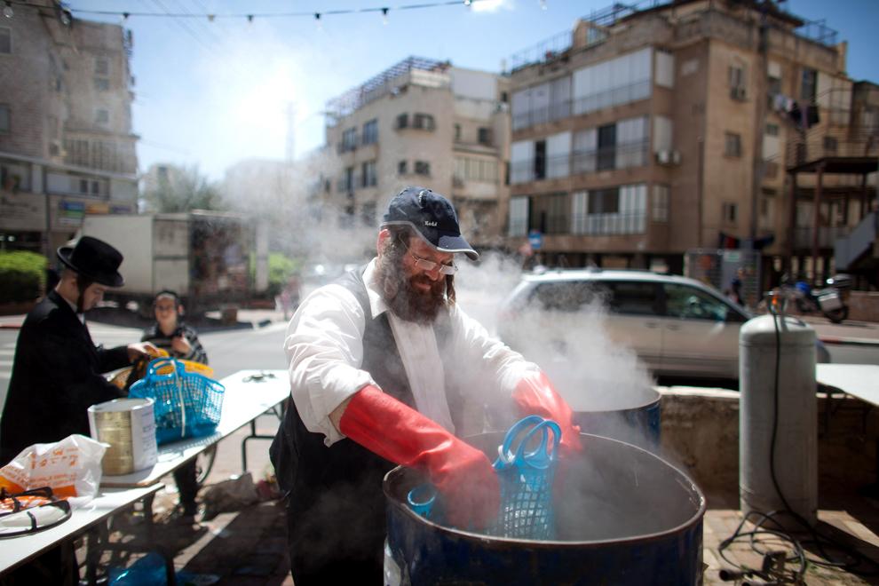 Un evreu ultra-ortodox ia parte la ritualul de purificare a ustensilelor de bucătărie în apă clocotită, pentru a le face cuşer, pentru sărbătoarea Pesach (Pastele), duminică, 24 martie 2013, în Bnei Brak, Israel.